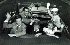 family waving from car