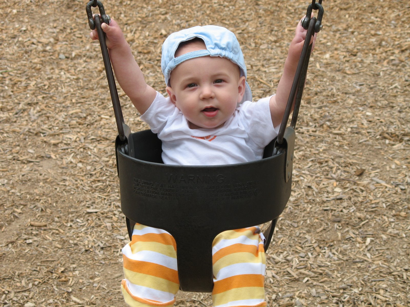 Man swinging baby by arms